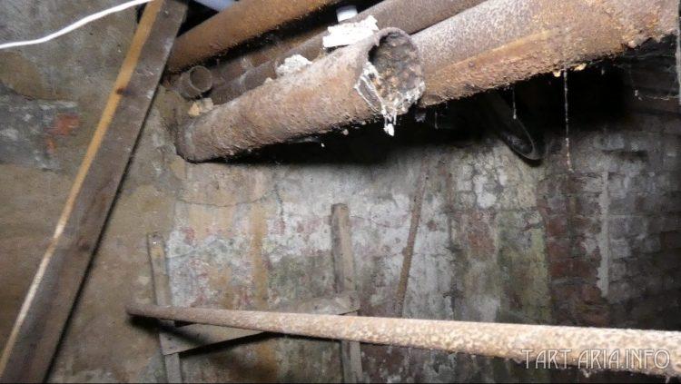 Трубы выходят из здания, через старое окно, которое уже под землёй.