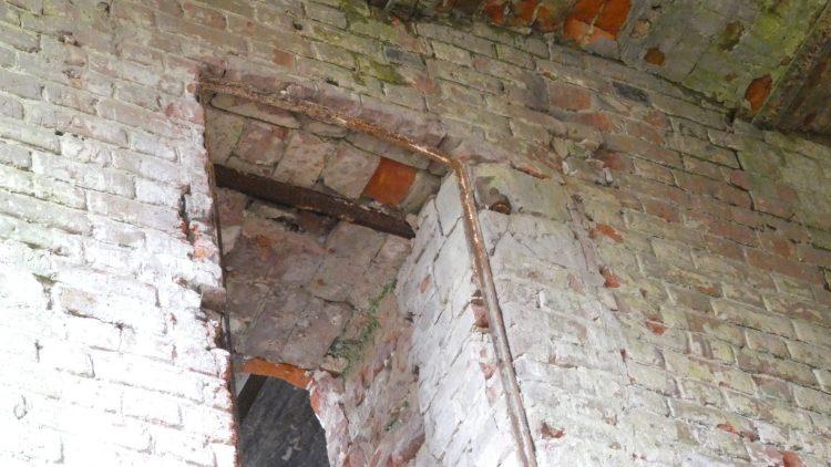 В стене, в пробитом дверном проёме, видна стяжка
